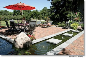 Outdoor patio and water feature shaded by an umbrella.