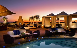 Outdoor pool lounge at sunset.