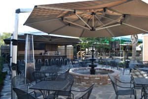 Outdoor restaurant seating with large patio umbrellas providing shade.