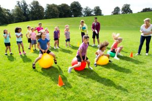 Field day event kids racing on space hoppers